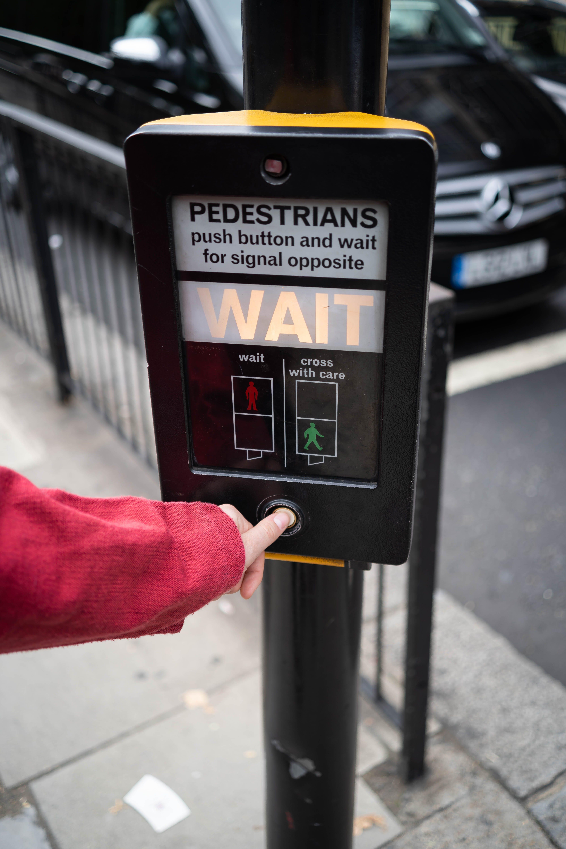 Photo of Person Pressing the Button of Pedestrian Box