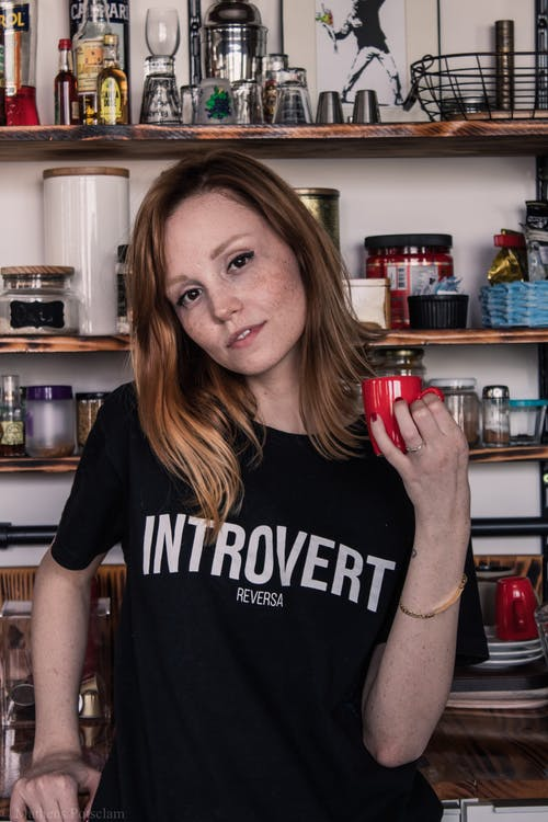 Photo of Woman Holding Red Coffee Cup Posing In the Kitchen