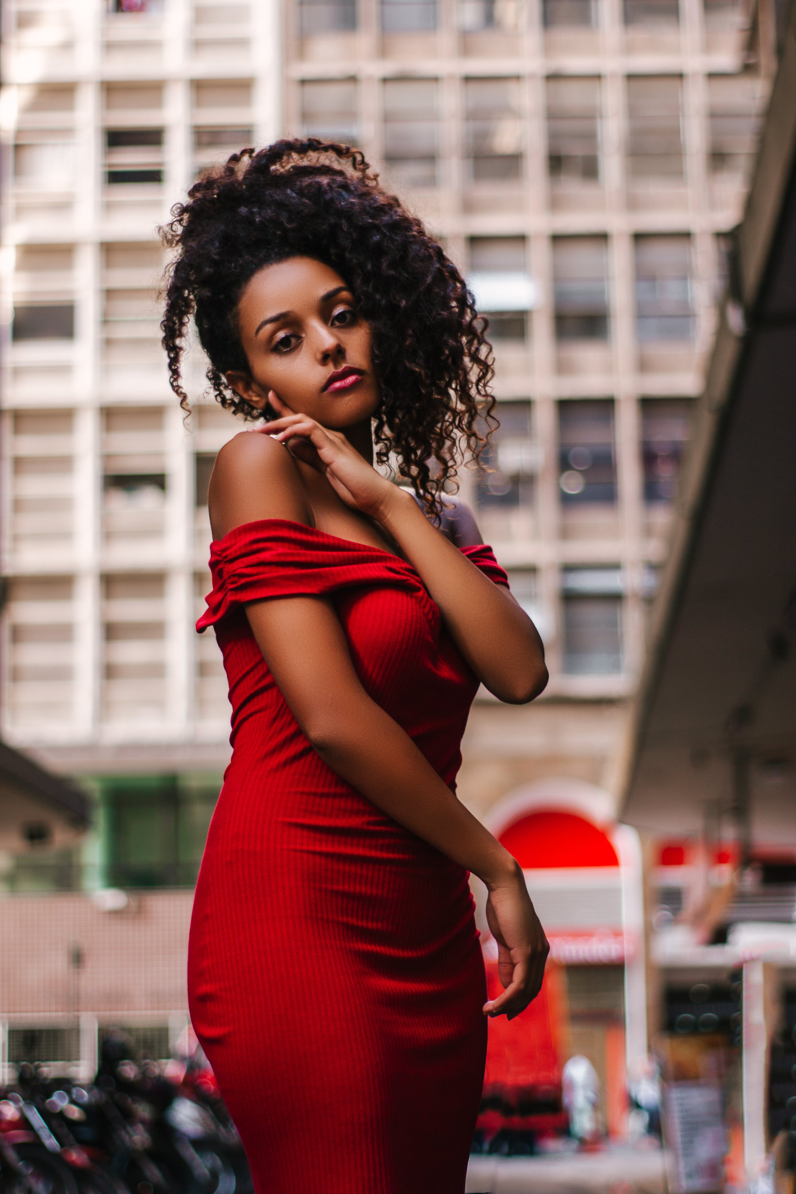 Woman in Red Off-shoulder Dress Near Building