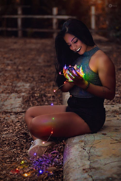 Woman Holding Turned-on String Lights