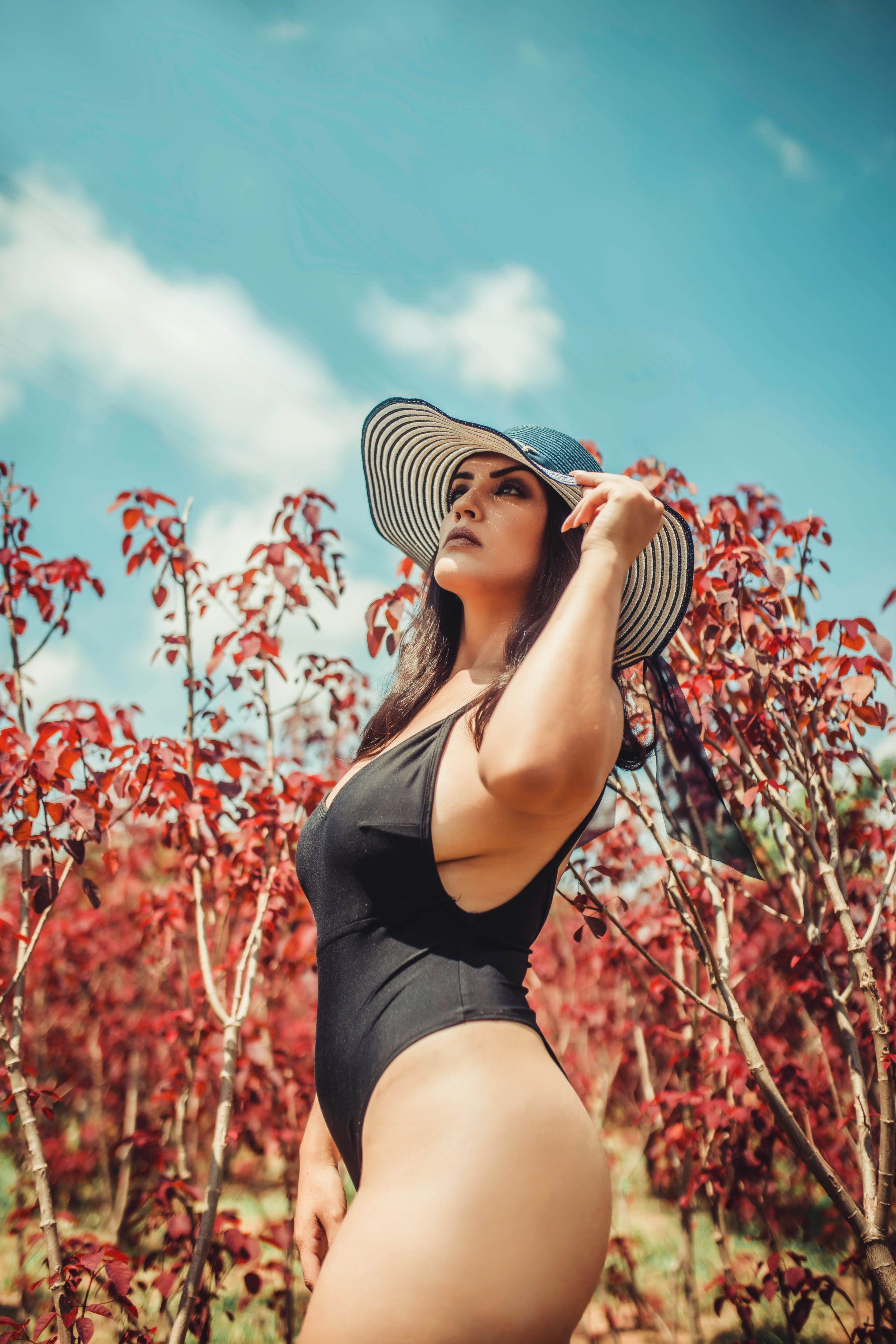Low Angle Photo of Woman in Black Monokini Beside Trees