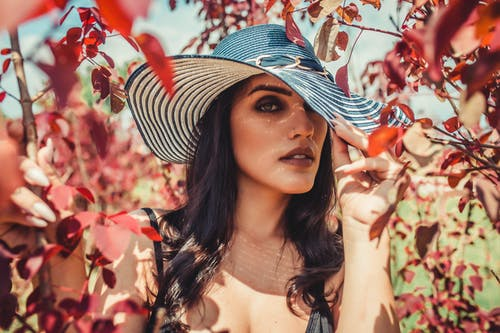 Woman Wearing Sun Hat While Being Surrounded by Red Leaves Outdoors