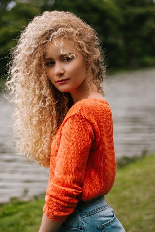 Curly Haired Blond Woman in Orange Shirt Glancing at Her Side