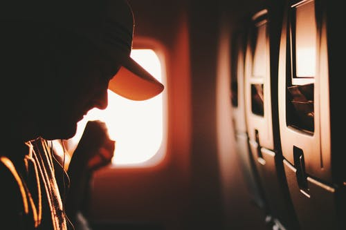 Man on Airplane Seat Wearing White Cap