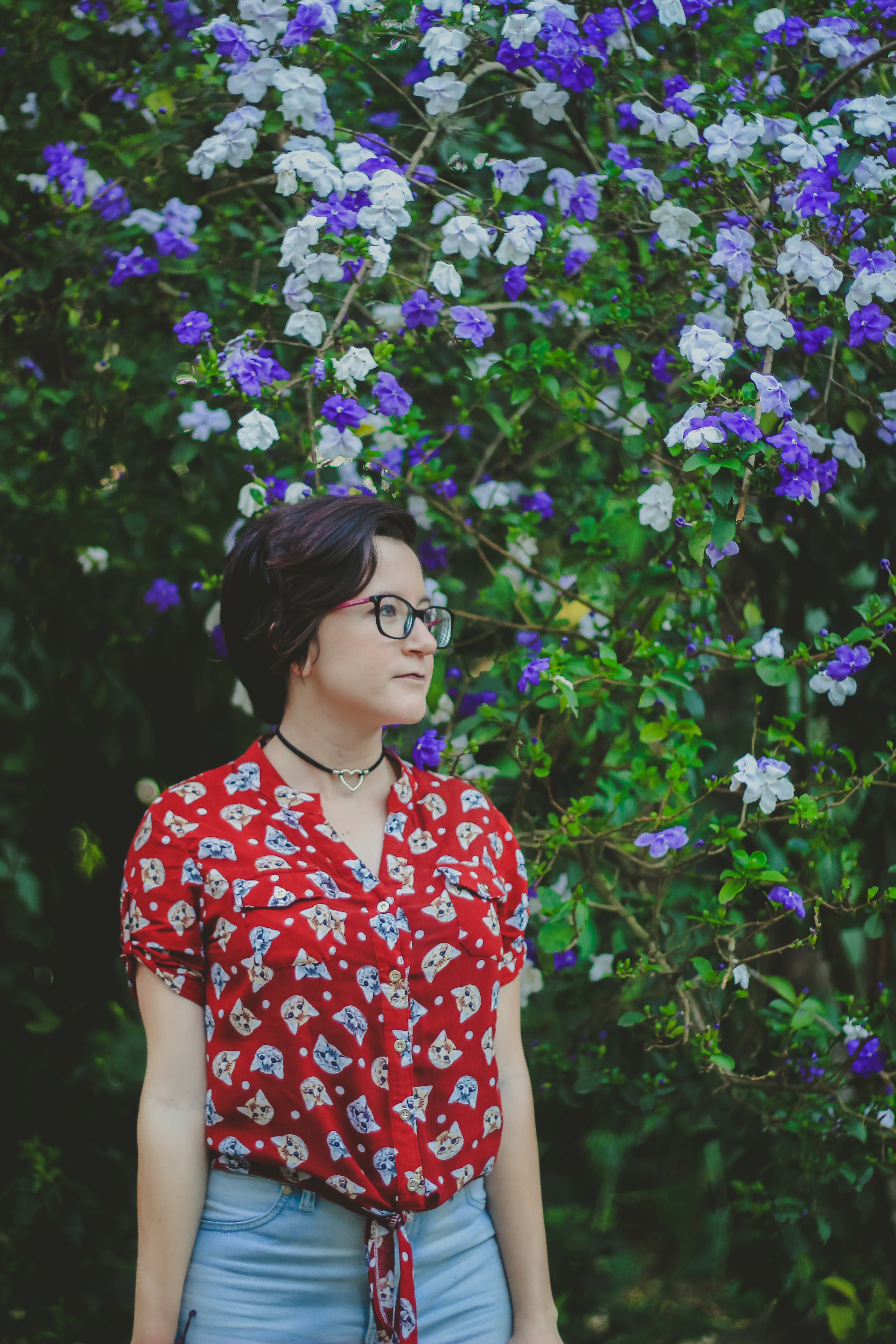 Woman Wearing Red and Blue Shirt Standing Beside Purple and White Flowers