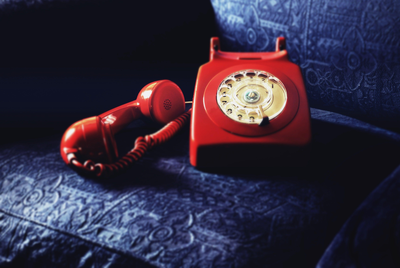 Red Rotary Telephone On Blue Sofa