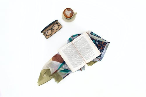 Composition of opened book cup of coffee and eyeglasses in case