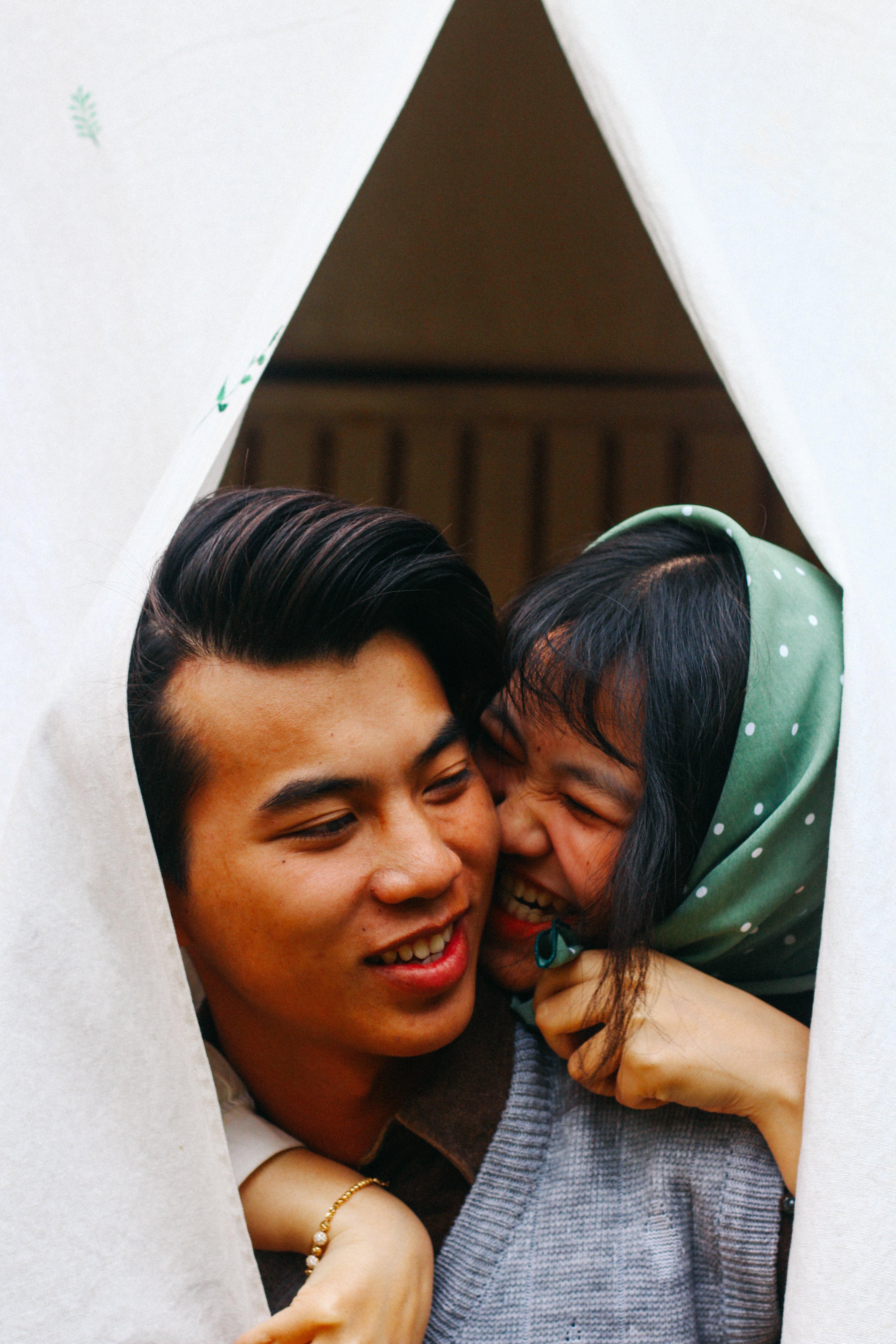 Woman Hugging Man in Gray Sweater