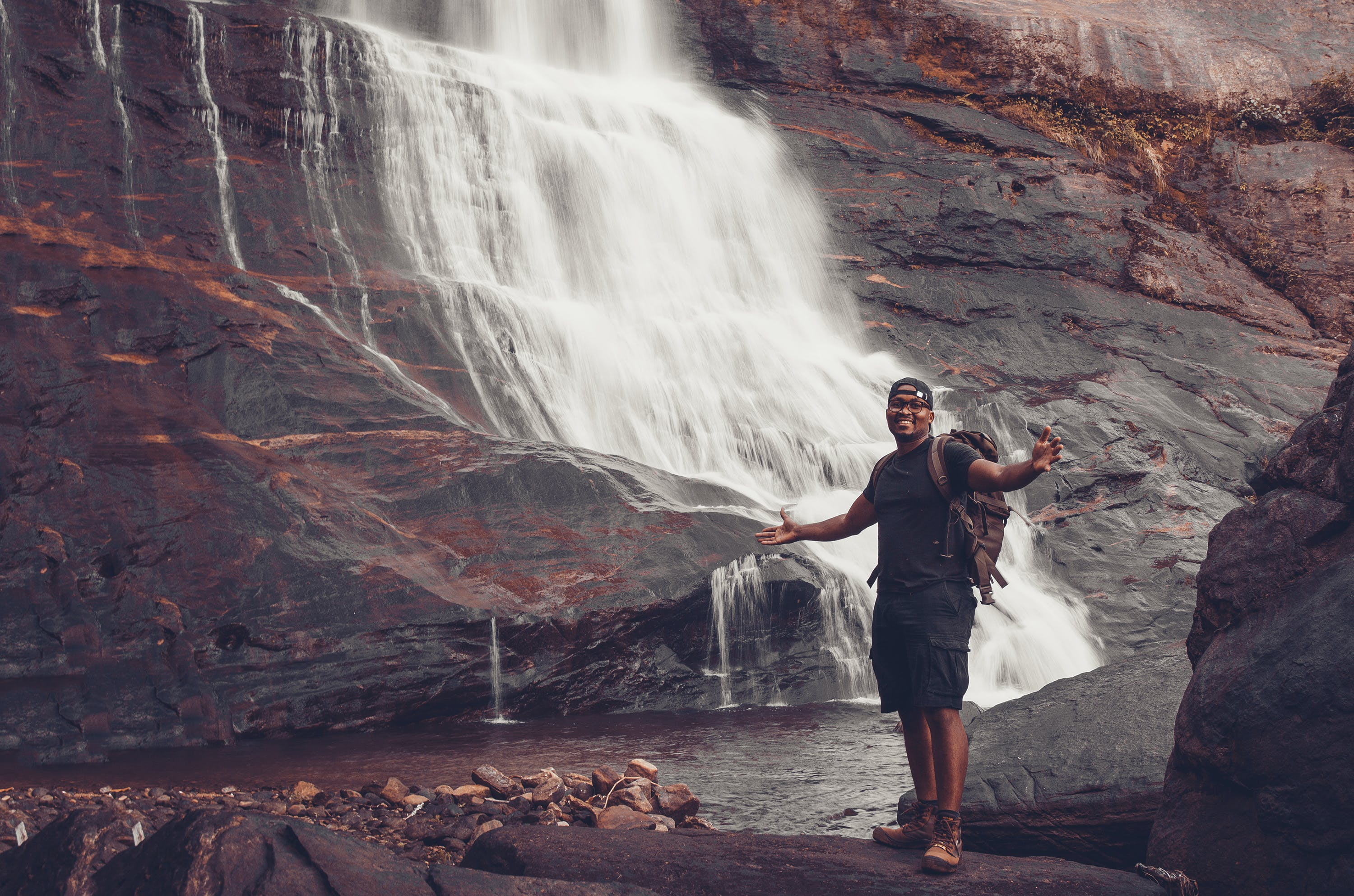 Photo of Man Standing Near Waterfalls