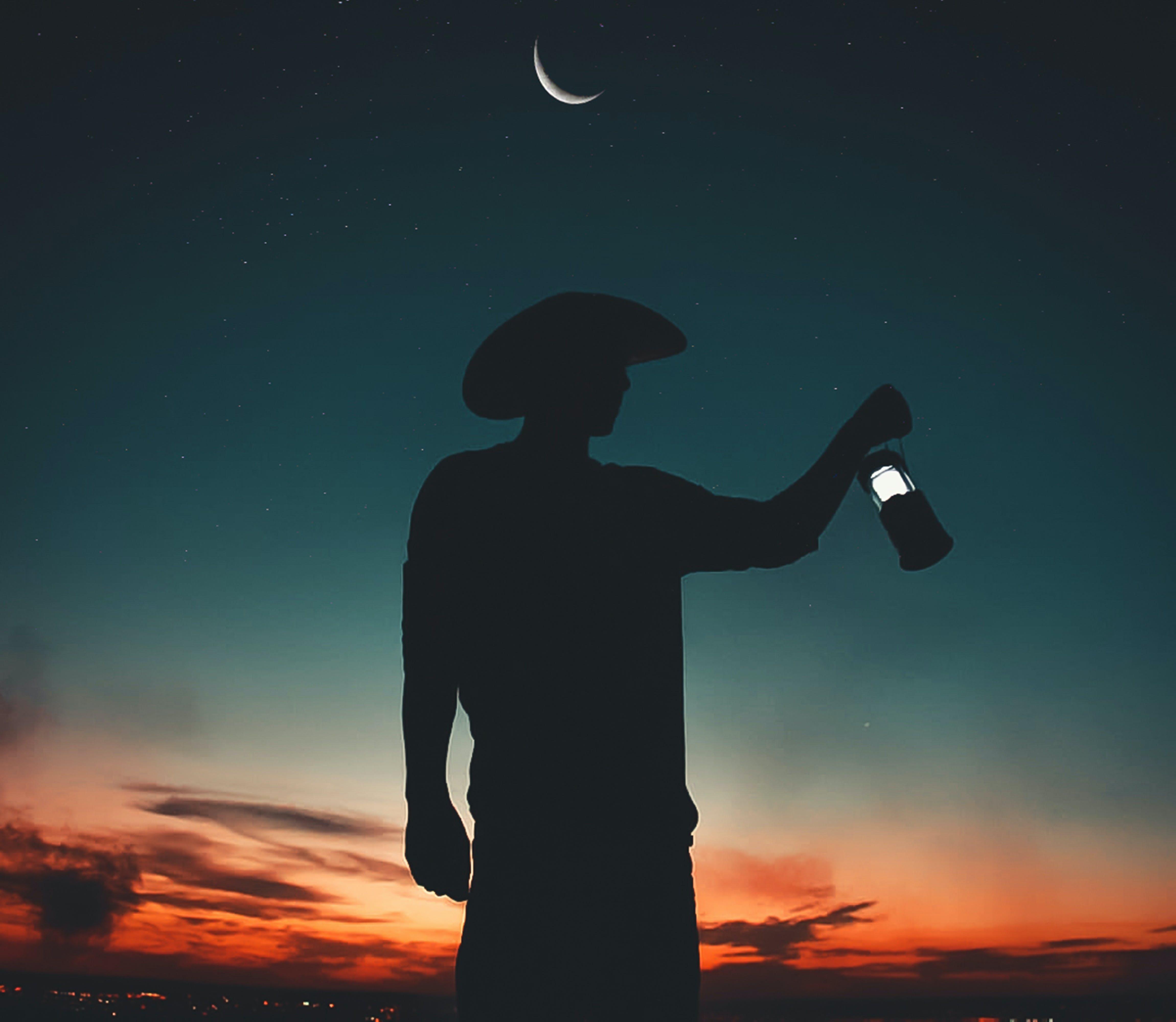 Silhouette Photo Of Man Holding Light Lantern