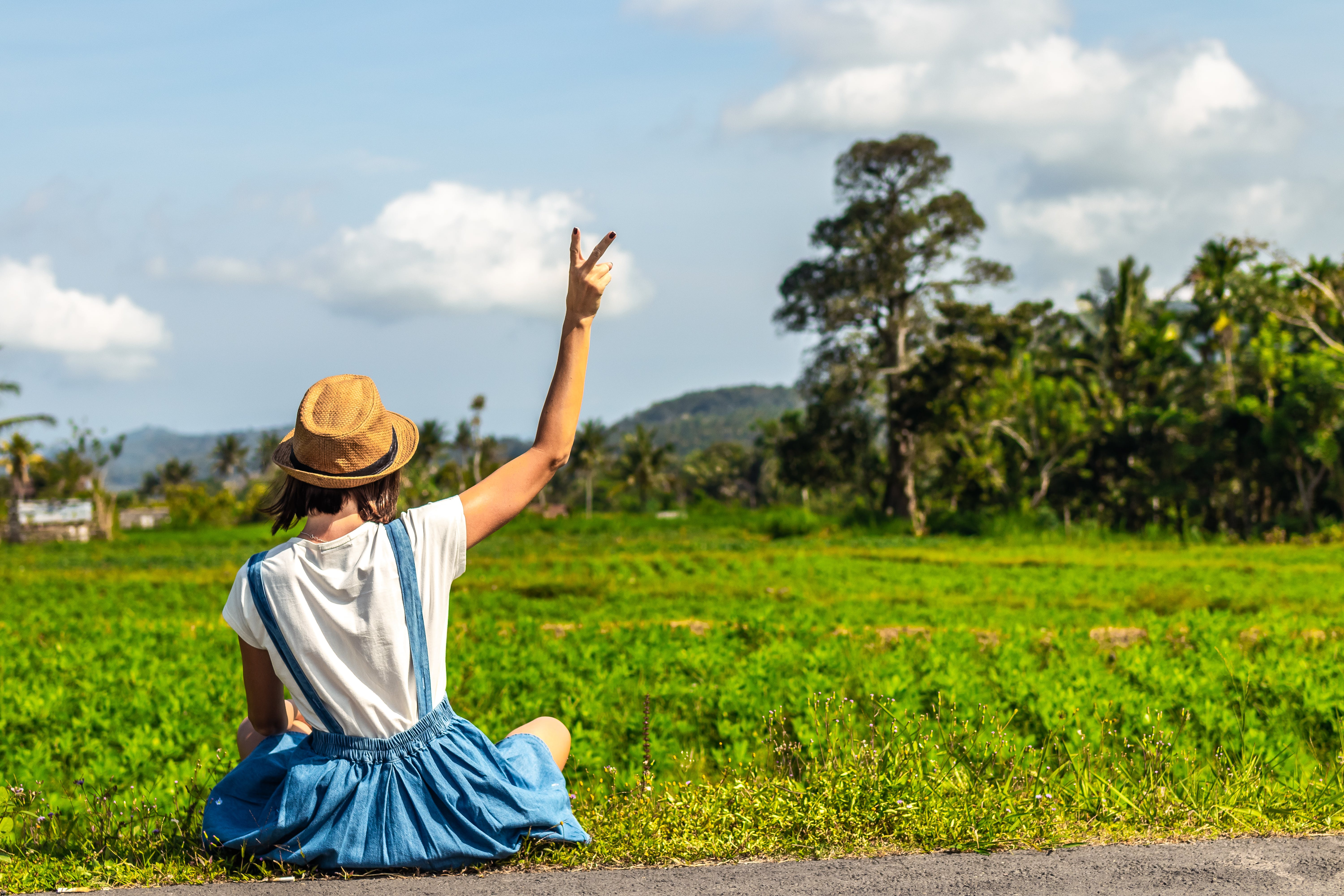 Woman Sitting Near Grass Field Showing Peace Hand Sign