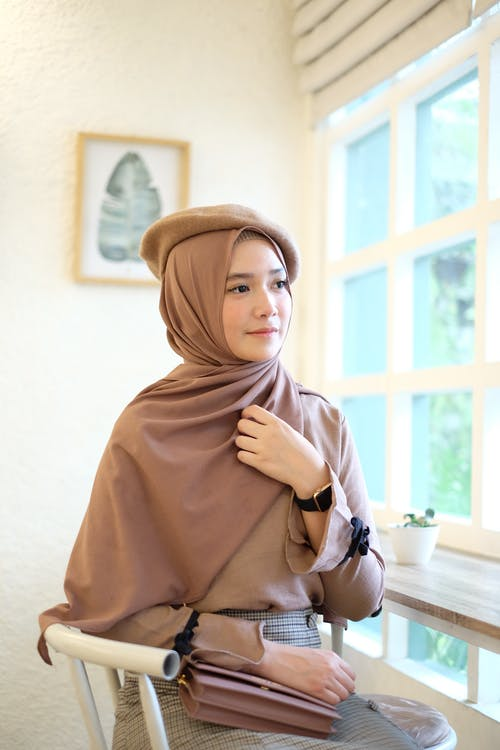 Woman Holding Hear Headscarf While Sitting
