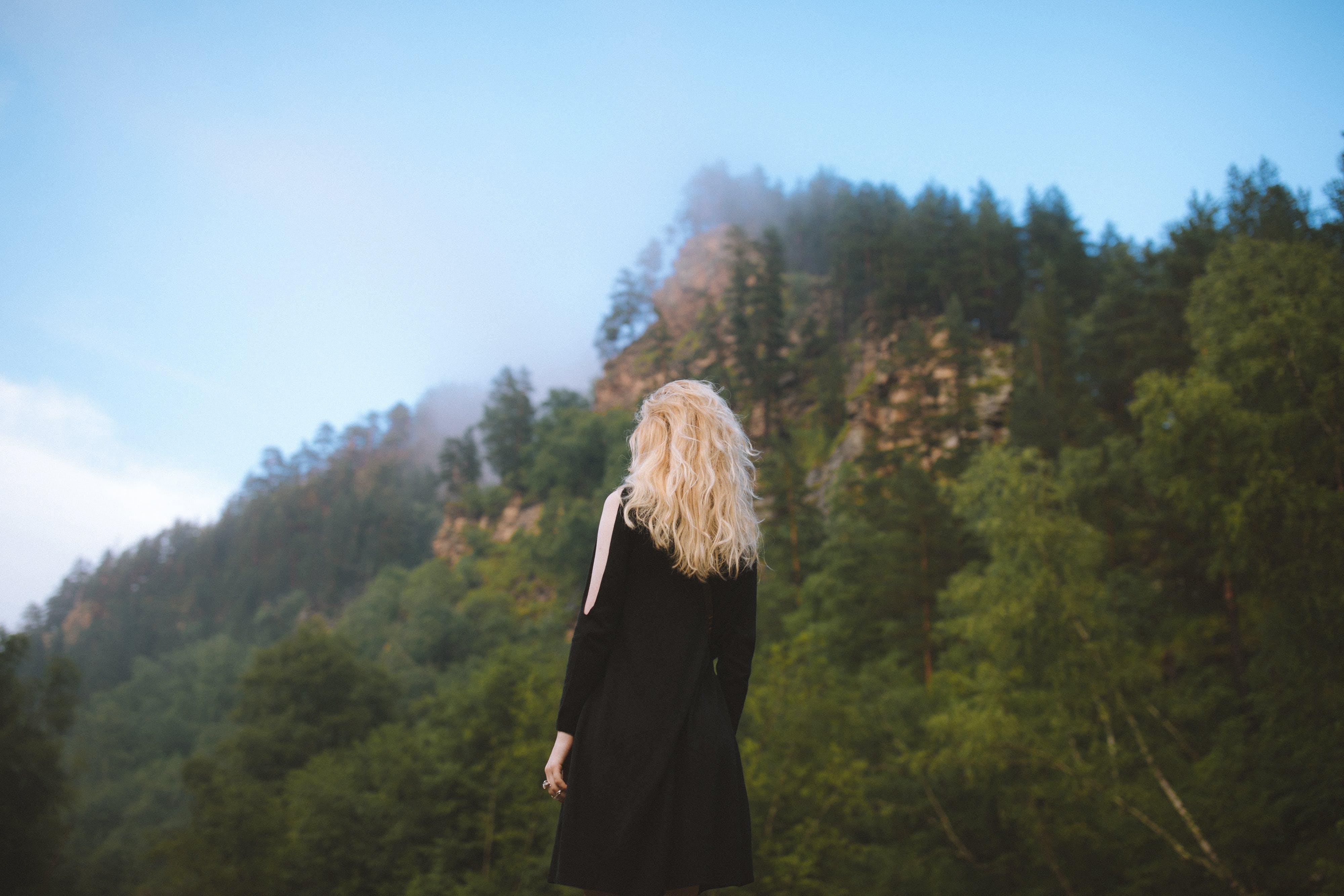 Selective Focus Photography of Woman Facing Mountain