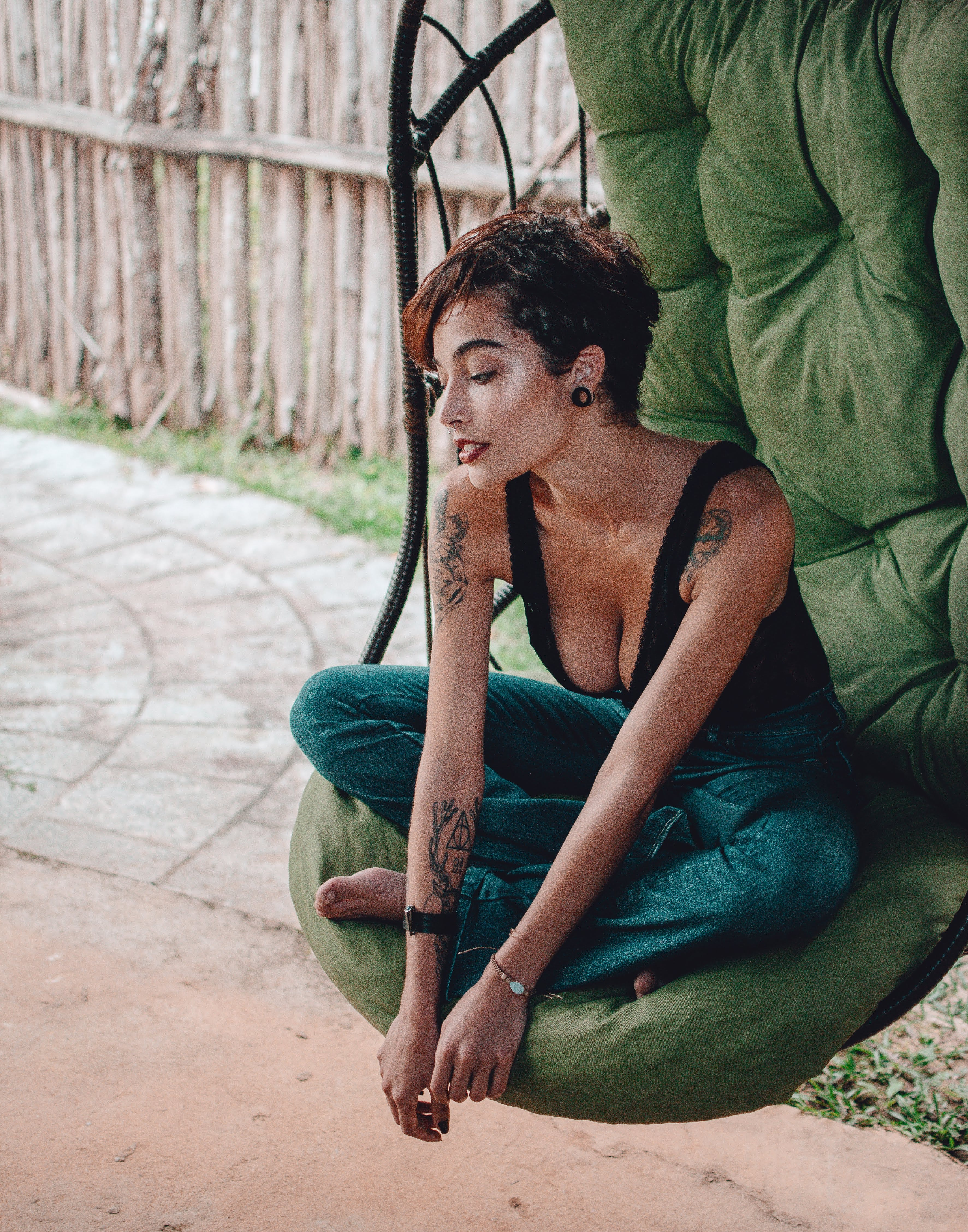 Woman Sitting on Hanging Egg Chair Near Wooden Fence