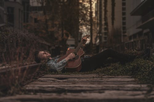 Man Lying Down on Ground While Playing Guitar