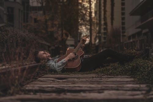 Základová fotografie zdarma na téma akustická kytara, chlápek, denní světlo, fashion modelka
