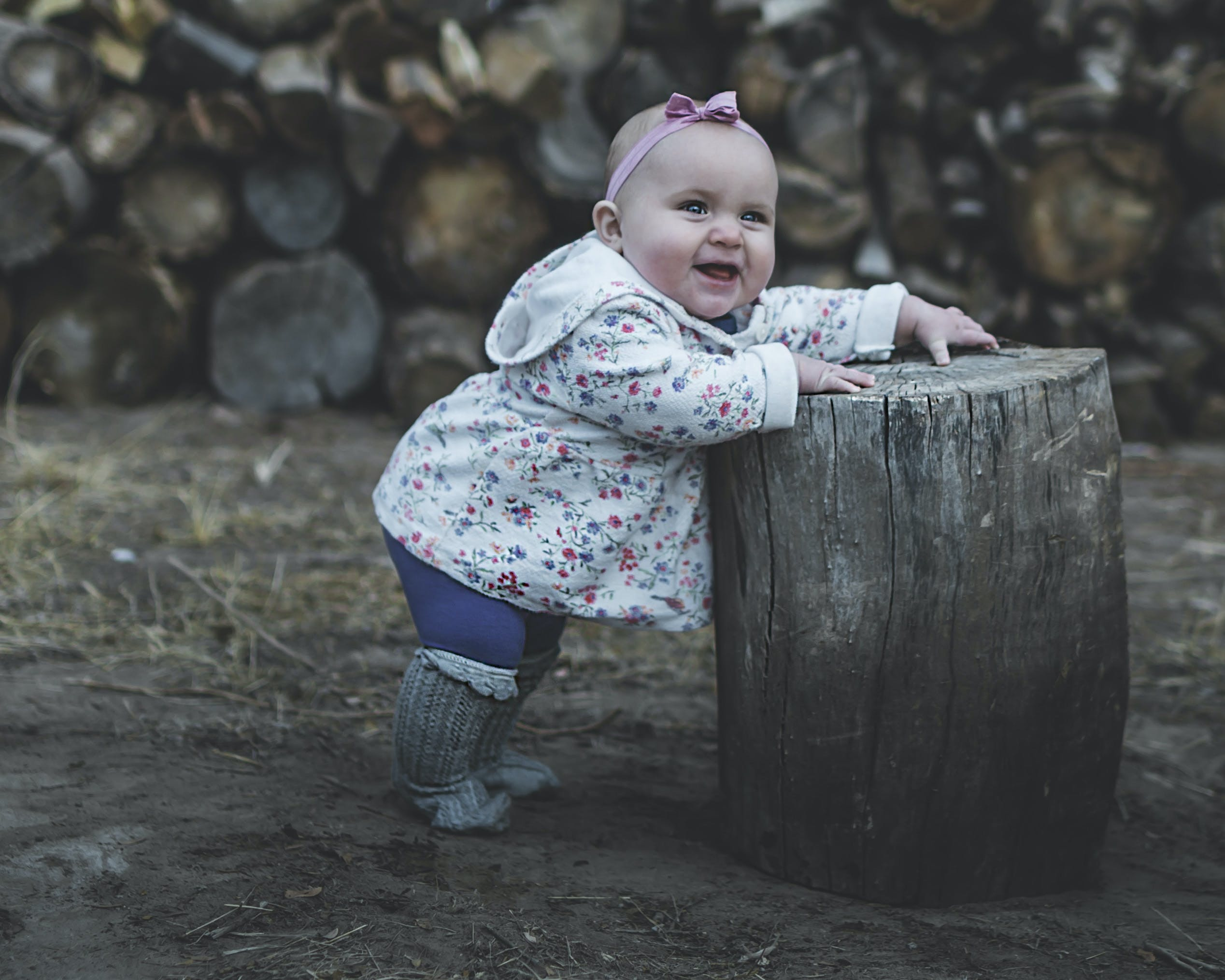 Toddler Standing and Leaning Against Log