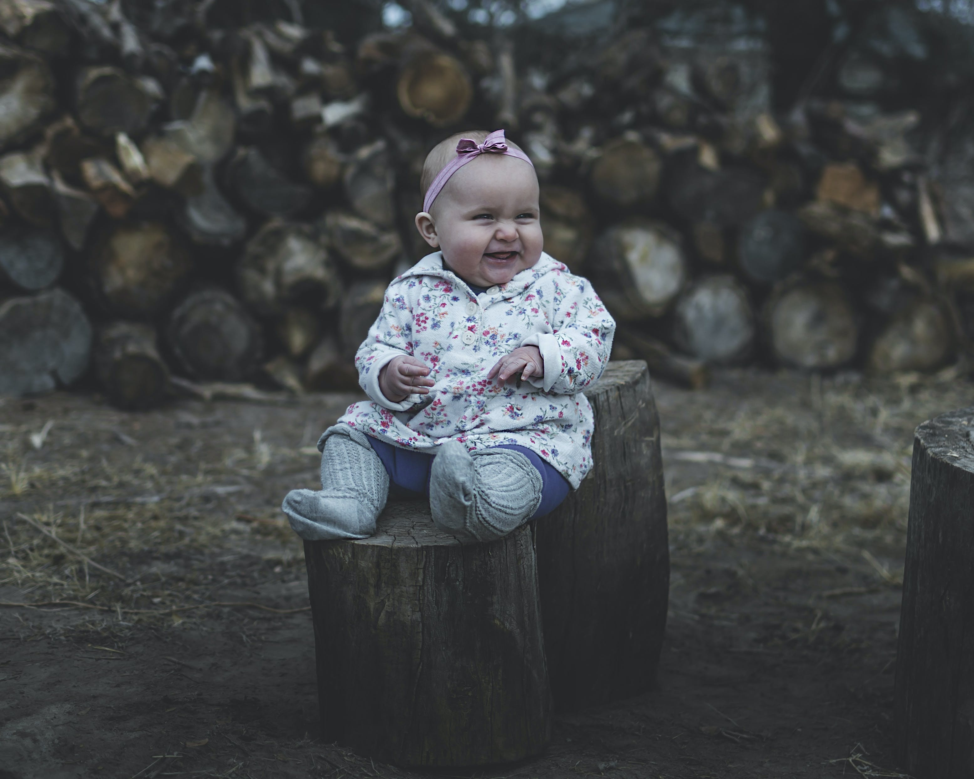 Toddler Smiling While Sitting on Wood Log