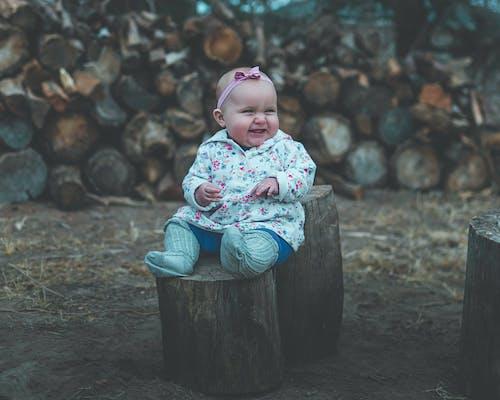 Toddler Smiling While Sitting on Wood Log