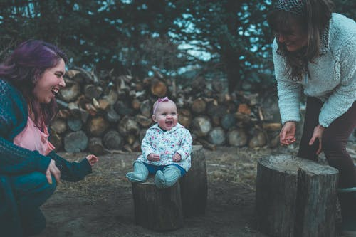 Smiling Baby Sitting on Cut Tree Log