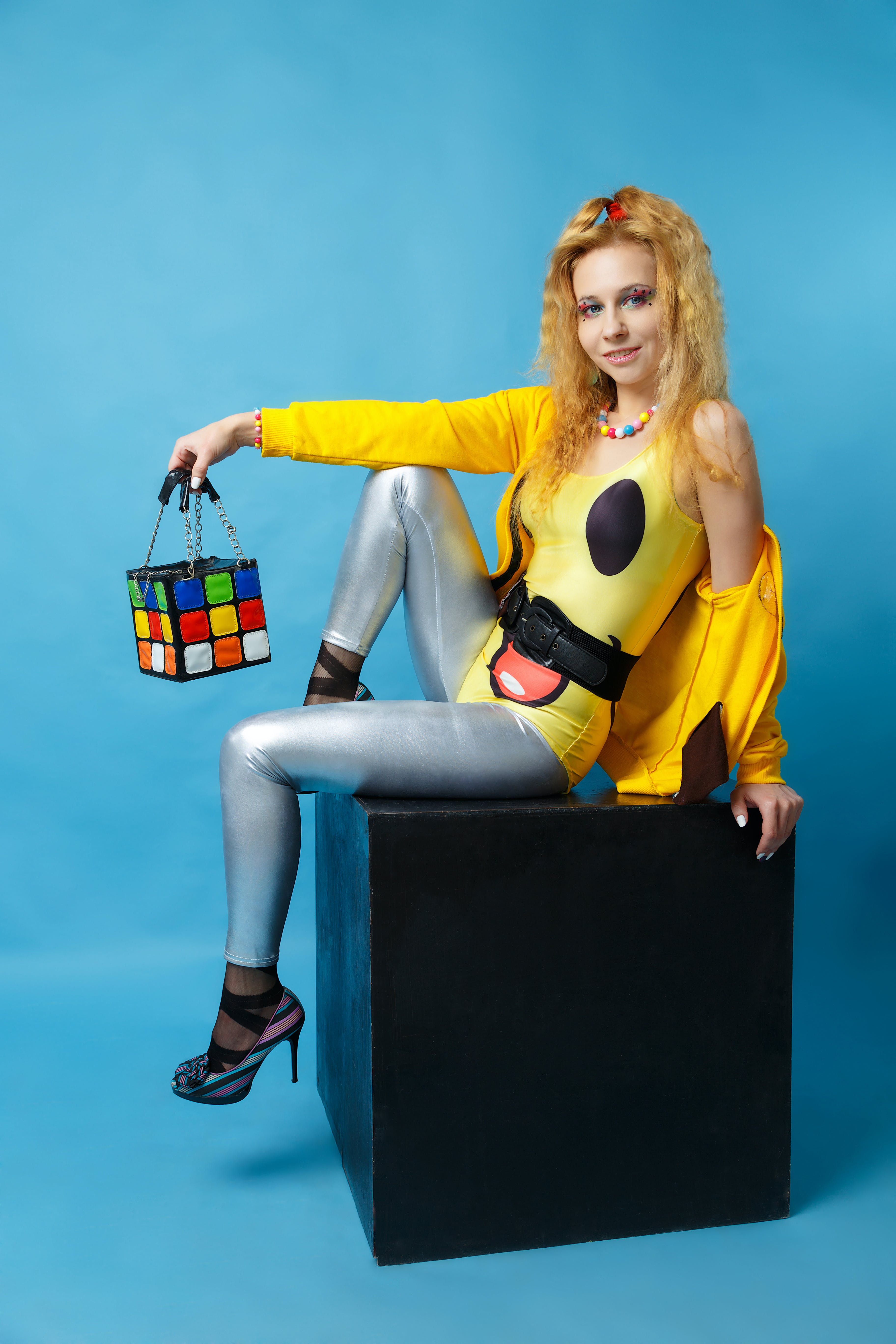 Woman Wearing Yellow Jacket And Grey Pants Sitting On Black Cube