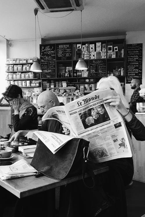 Monochrome Photo Of Person Holding Newspaper