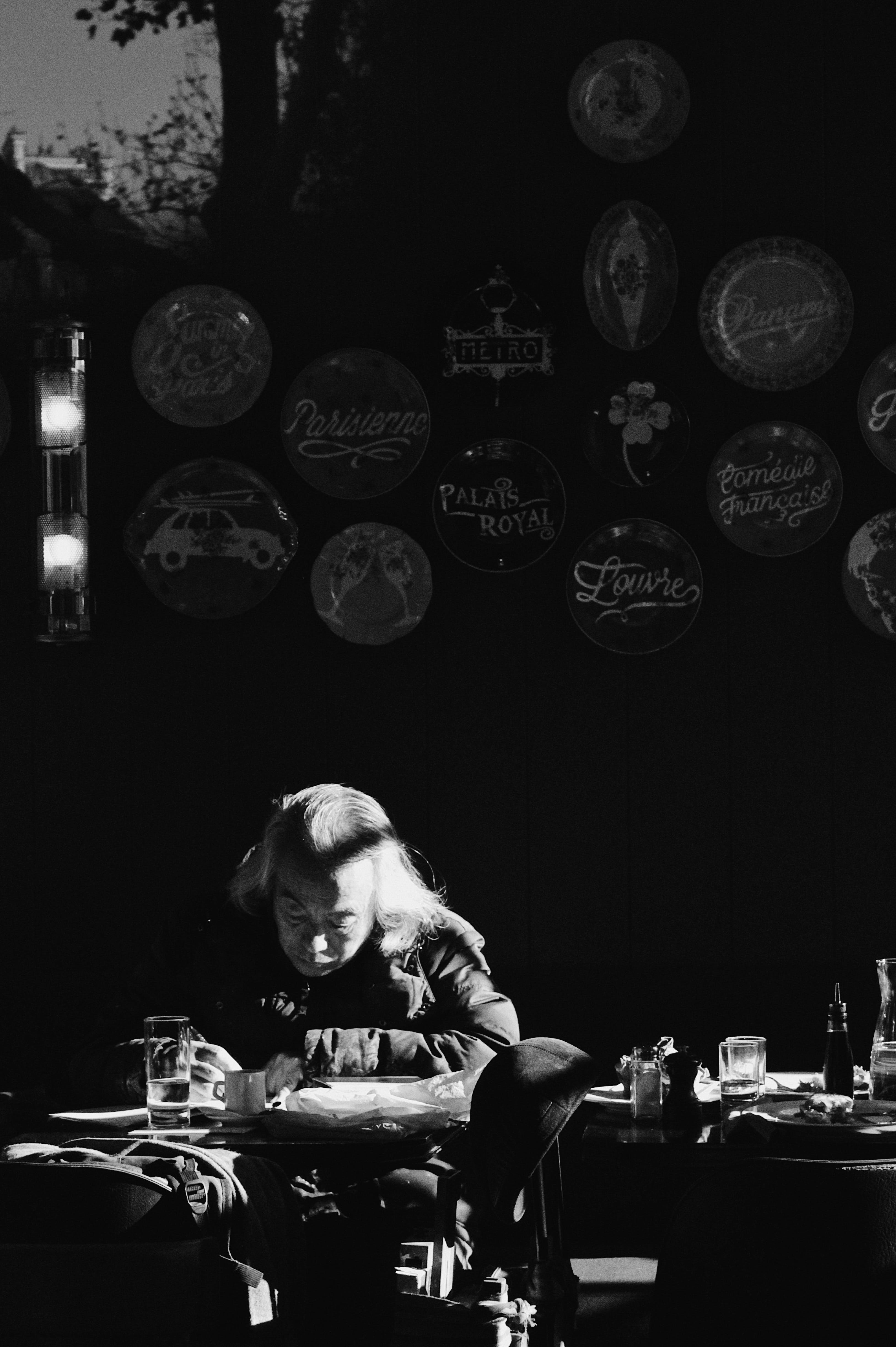 Man Writing on Desk Grayscale Photography