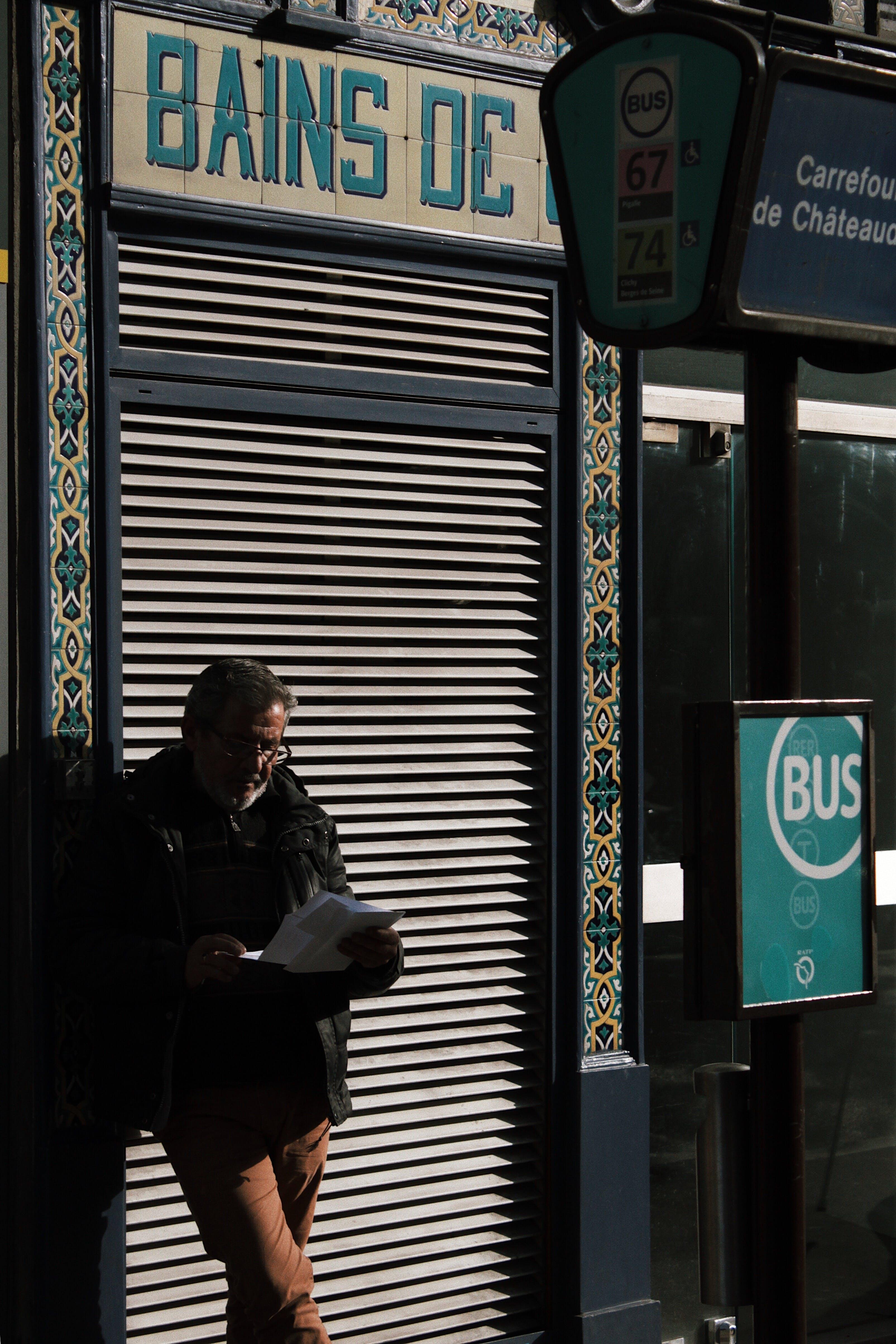 Man Reading Newspaper in Street