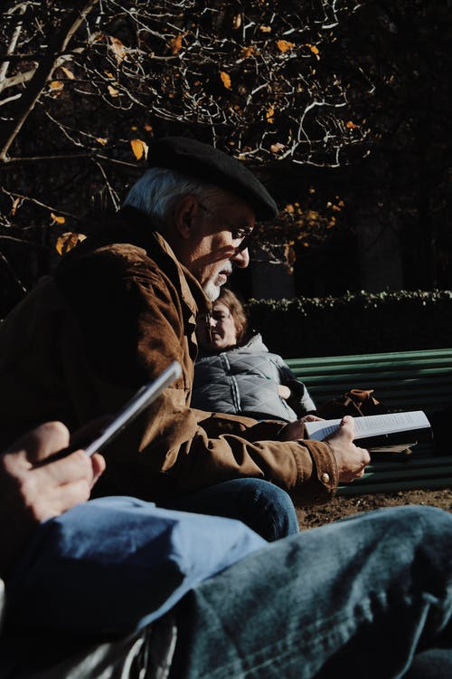Thoughtful old man reading book in park