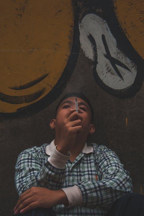Man Smoking Near Graffiti Filled Wall