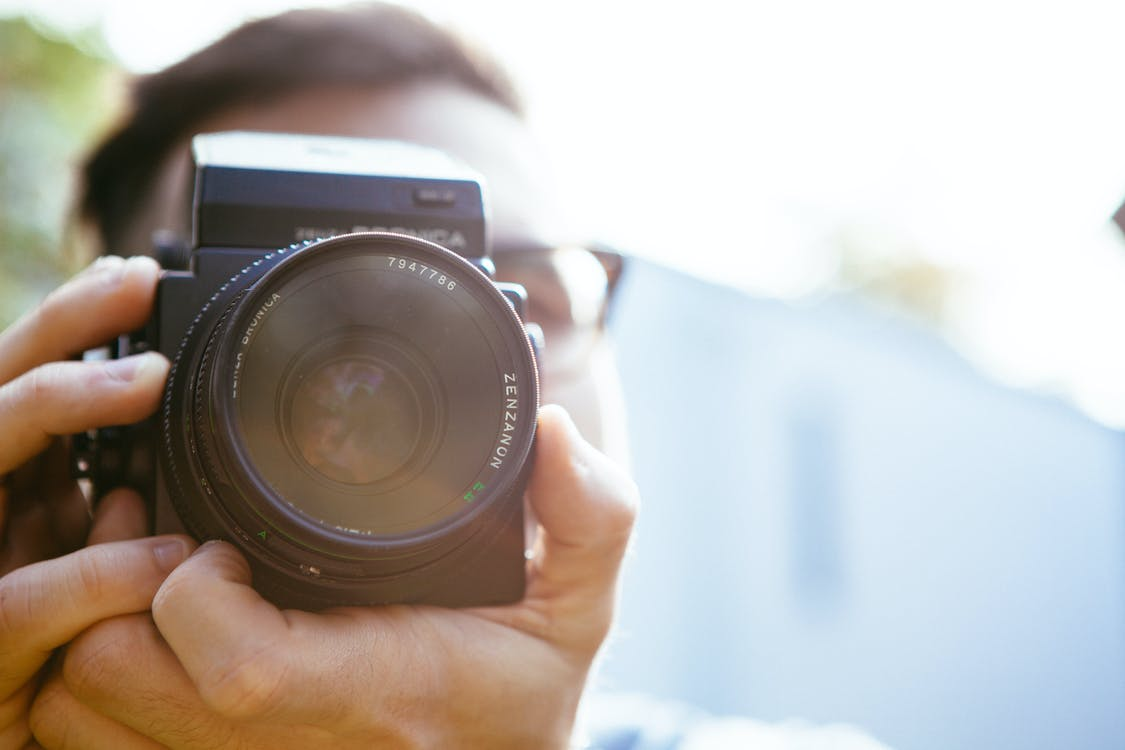 Person Holding Camera during Dayime