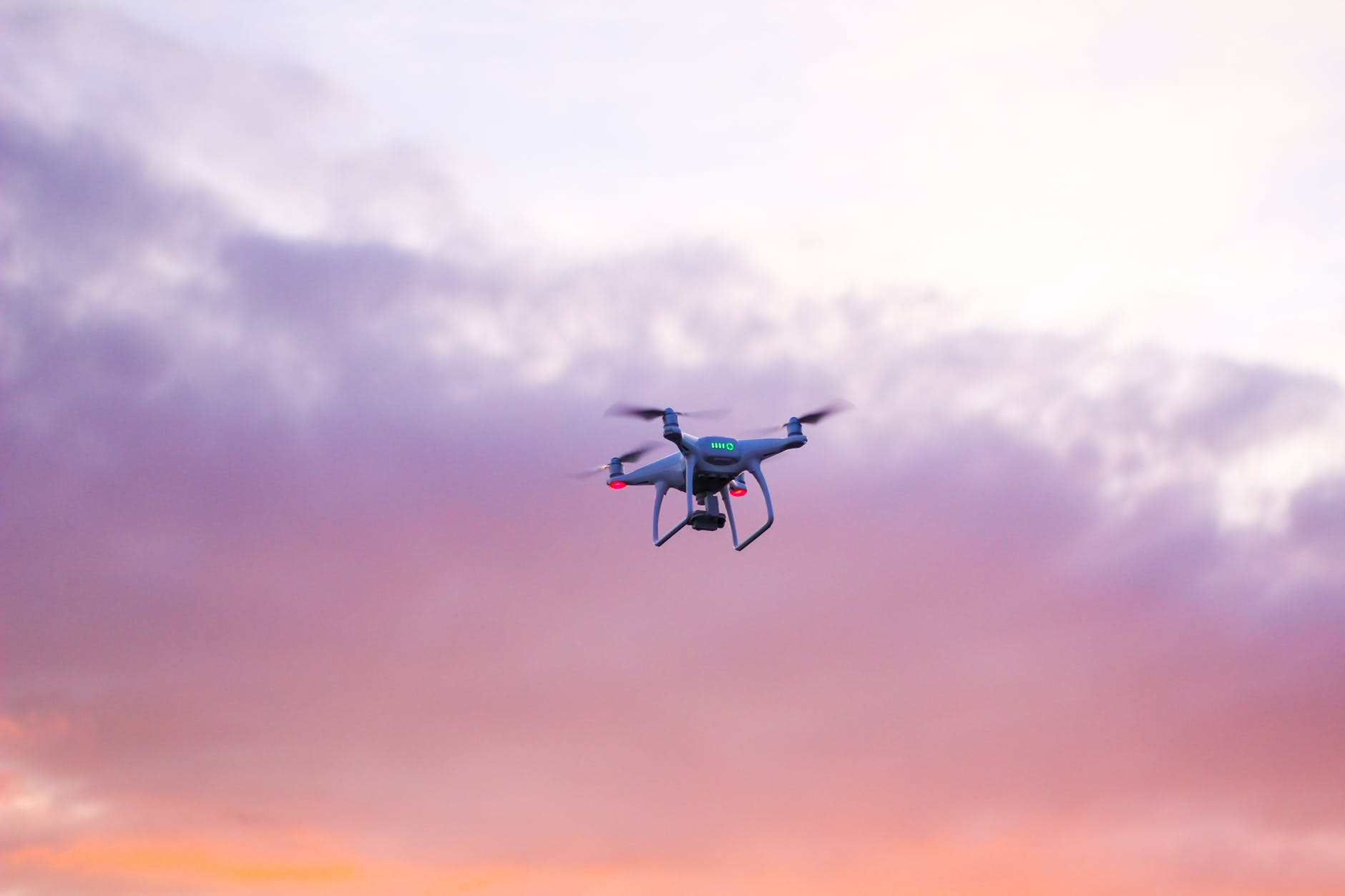 drone mid-air against the purple and orange clouds