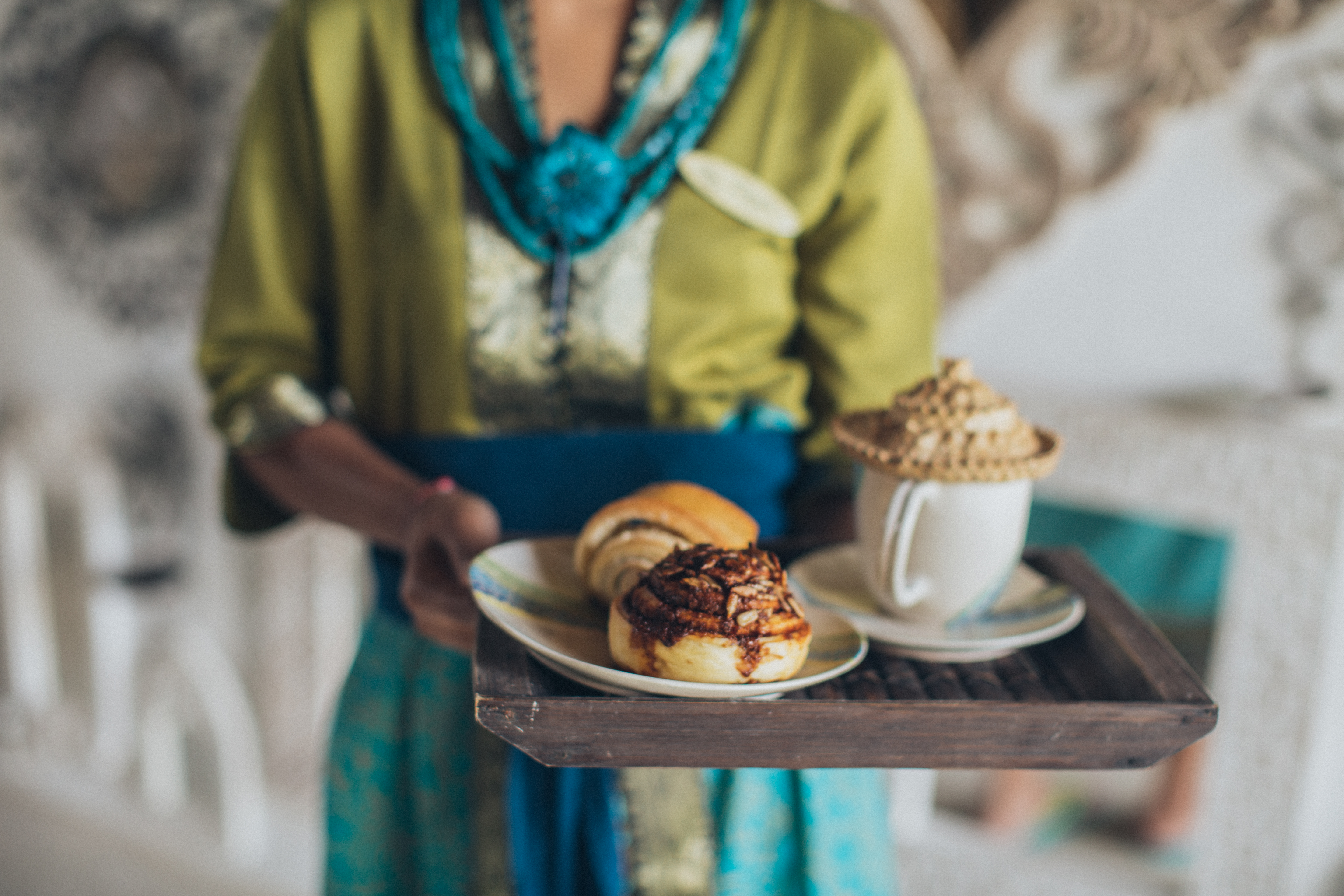 Woman Serving Plate of Cinnamon Breads and Cup of Beverage