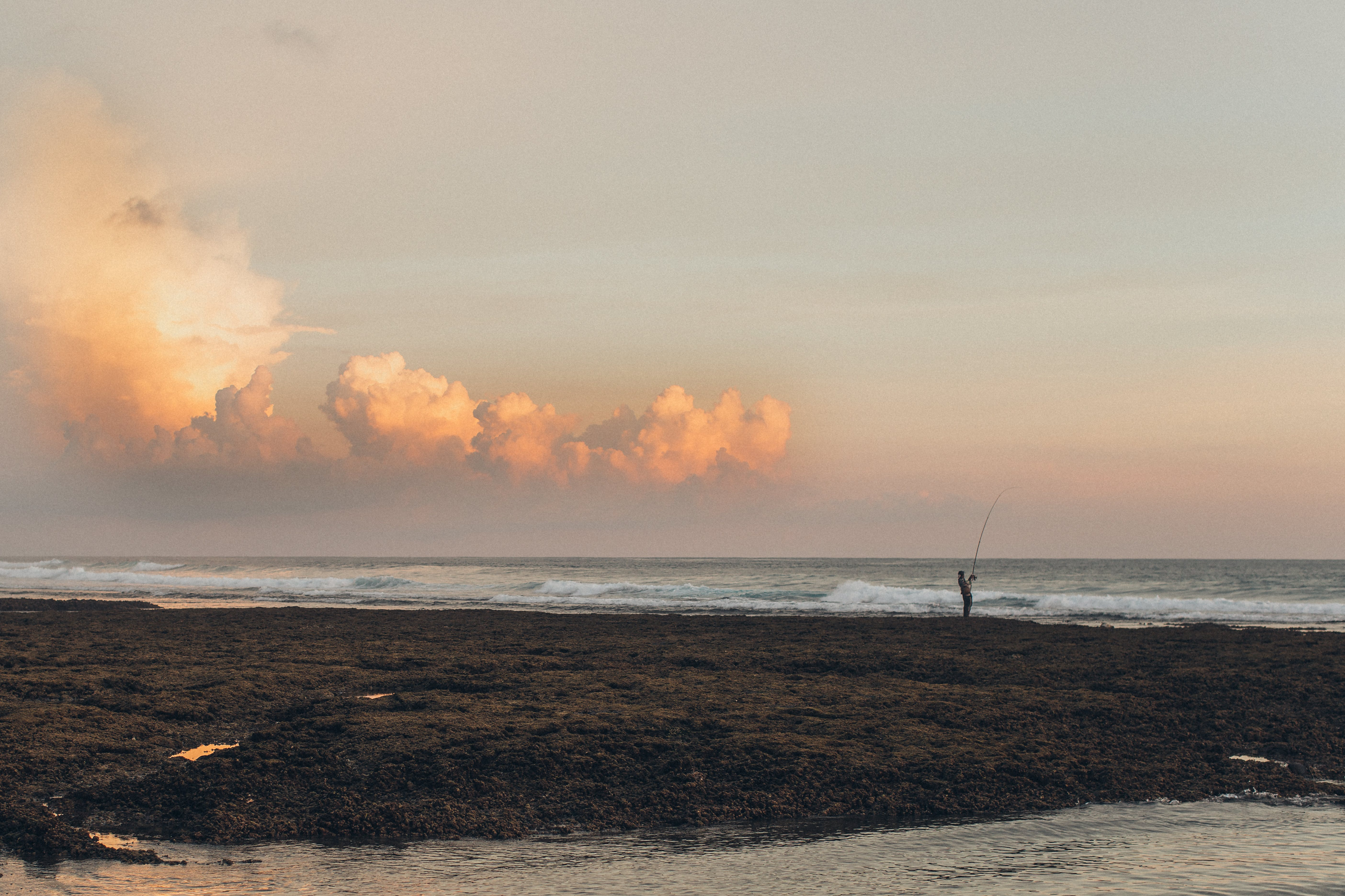 Person Fishing At Shore During Golden Hour