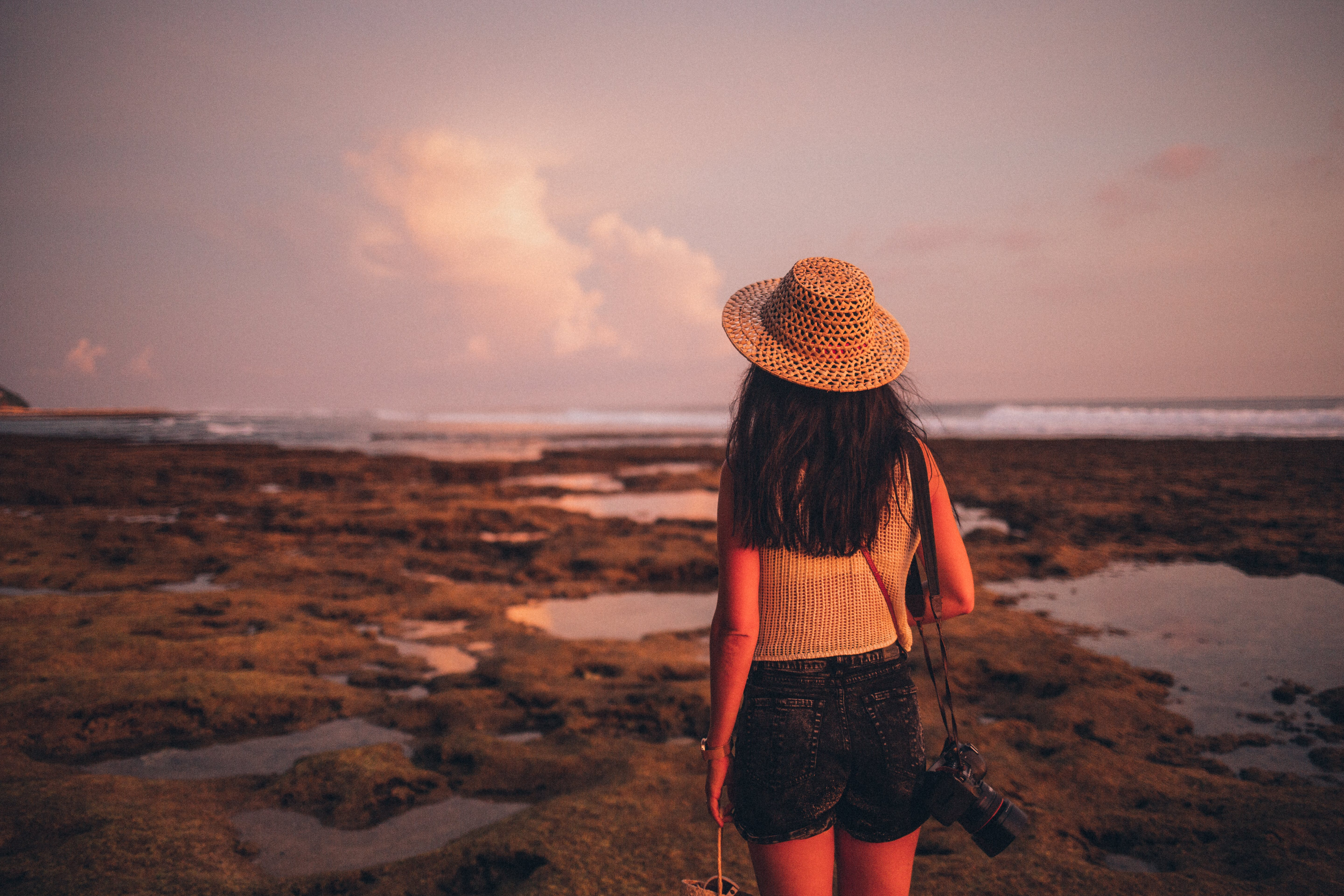 Selective Focus Photography of Woman Standing on Seashore Facing Body of Water
