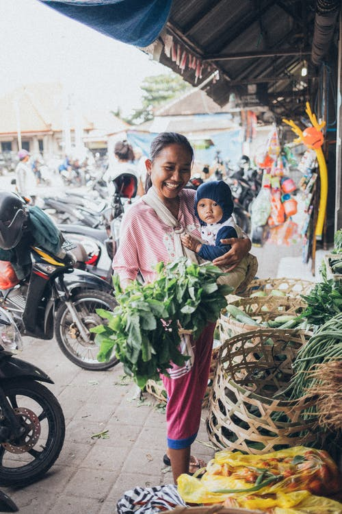 Smiling Woman Carrying Baby and Holding Green Leafy Vegetable