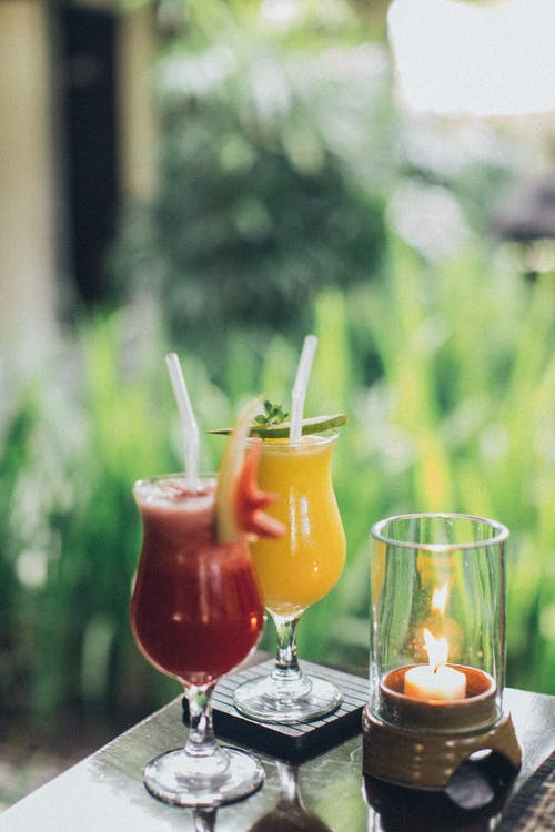 Two Clear Drinking Glasses Filled With Juice Selective Focus Photography