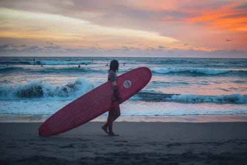 Man Carrying Surfboard Walking On Seashore