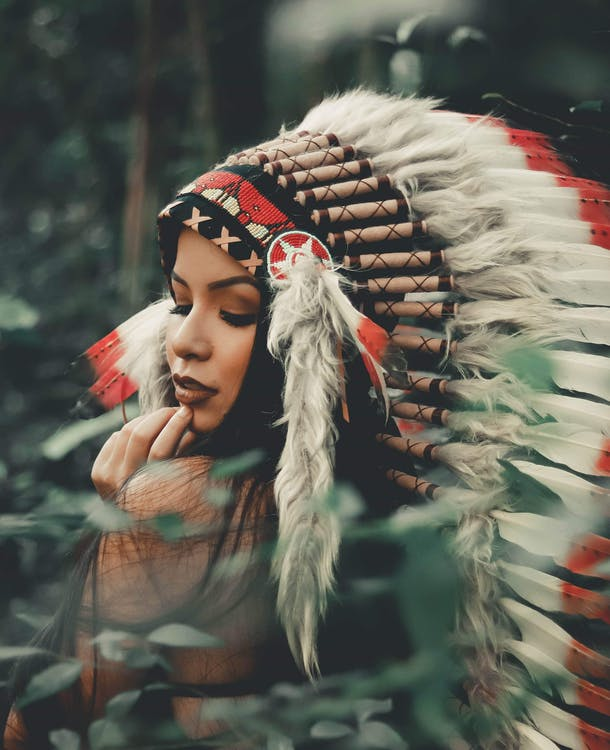 Selective Focus Photography of Woman Wearing Native American Headdress