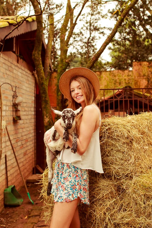 Smiling Woman Holding White and Black Animal Beside Hay