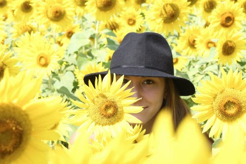 Selective Focus Photography of Girl Standing Near Sunflower Field