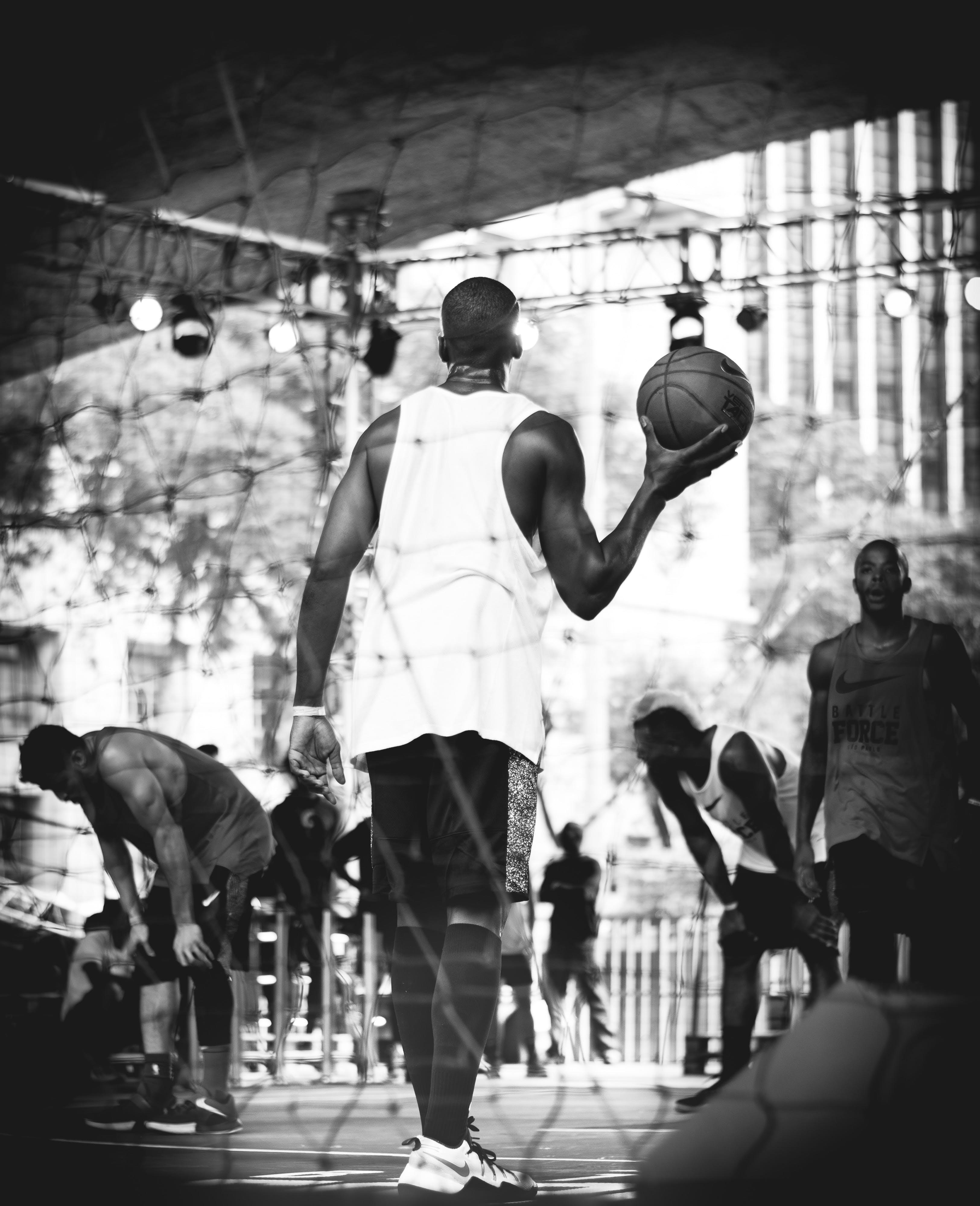 Grayscale Photography of Man Holding Basketball Ball