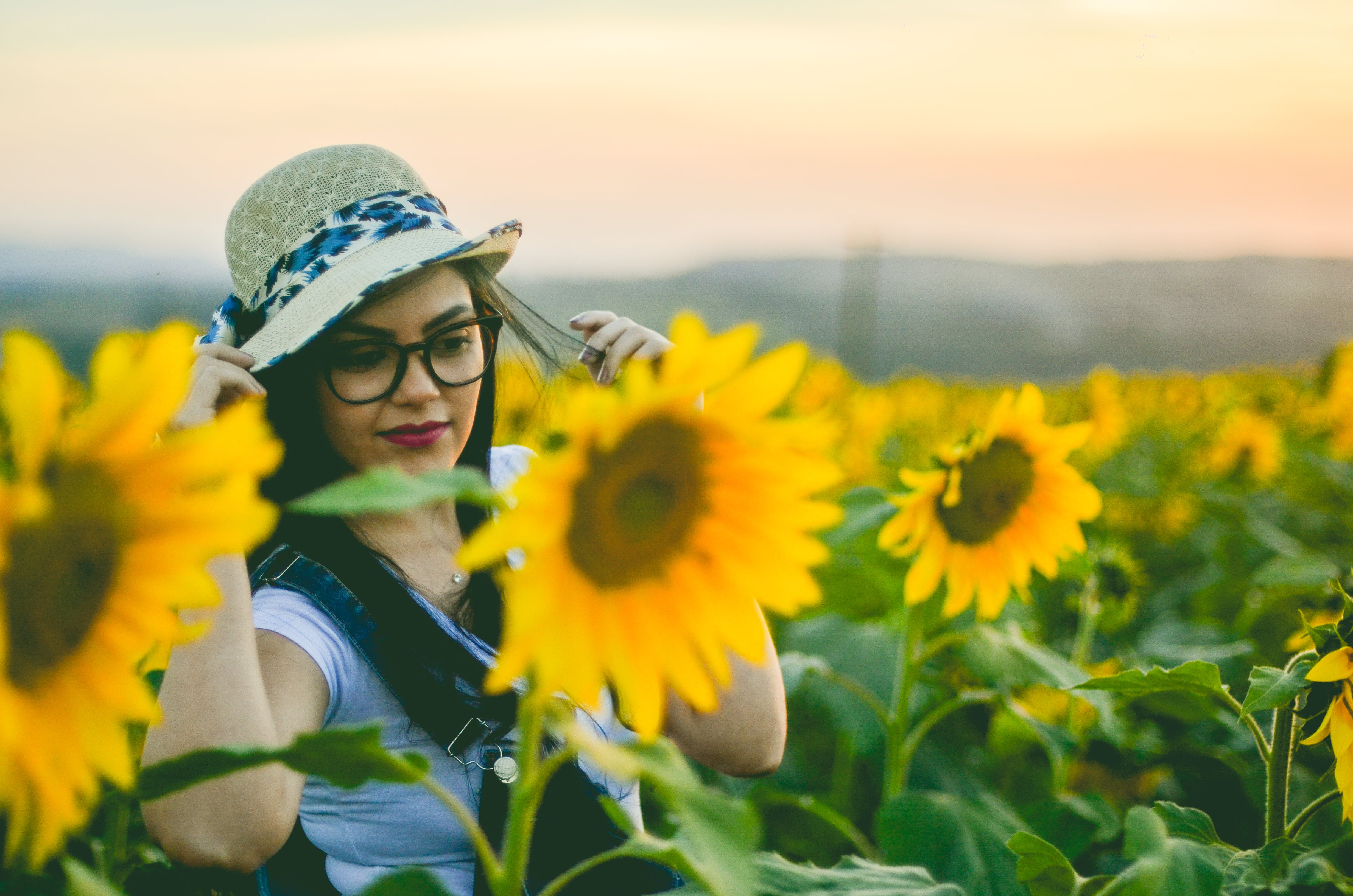 Woman Standing Behind Sunflowers