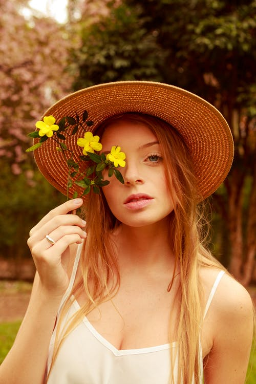 Woman Wearing Straw Hat Holding Yellow Flowers Near Her Face