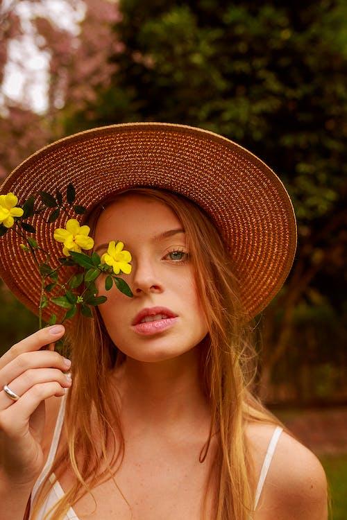 戴草帽,拿著黃色的花朵,靠近她的臉的女人