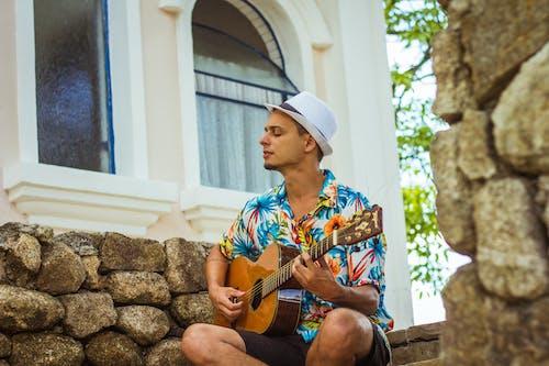 Man Playing Guitar Sitting on Concrete Steps
