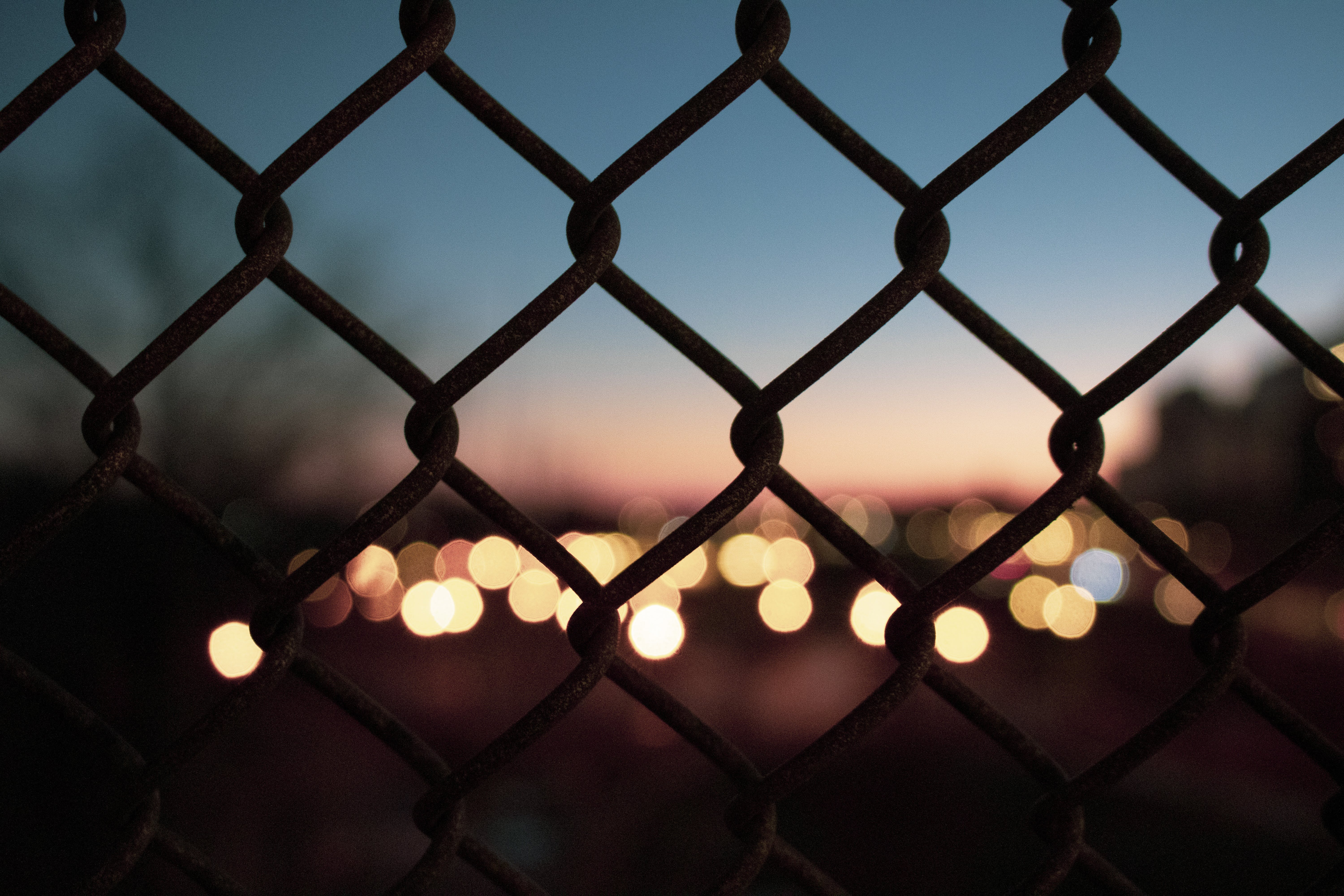 Selective Focus Photography of Silhouette Fence Near Bokeh Light