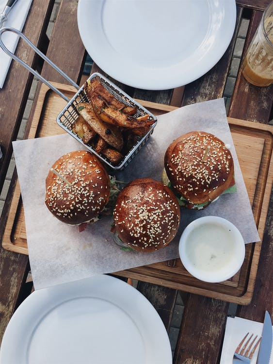 Three Burgers on Brown Wooden Tray Between White Ceramic Plate