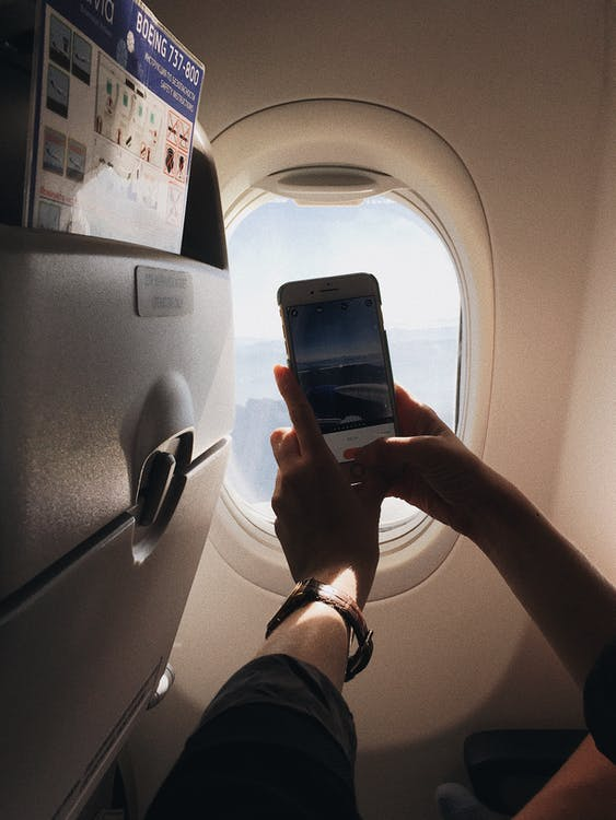 A woman holding a cellphone, taking picture of outside view through an airplane's window - International Air Travel