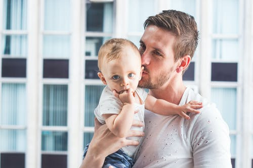 Man Holding and Kissing Baby